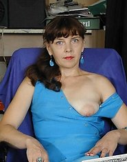 A mature lady poses in blue dress and stockings and then sucks
